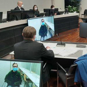 Rättegångssalen vid en mordrättegång. Rättens ordförande och två tingsdomare sitter bakom ett långt bord uppe på en avsats, åklagaren och försvarsadvokaten sitter vid varsitt bord. Den åtalade är med på rättegången via en videolänk från fängelset.