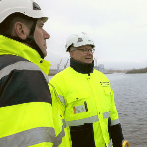 Tre män i gula västar och vita skyddshjälmar diskuterar i Raumo hamn.
