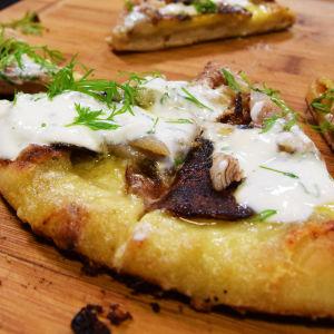Hemgjord pizza på skärbräde.