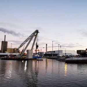 En pontonkran lyfter betongelement på plats i bassängen i Vasa hamn.