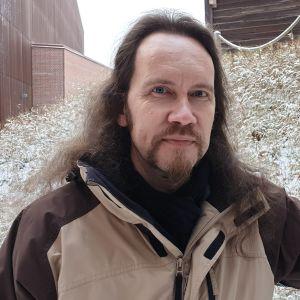 Mies seisoo ulkona talvisessa maisemassa