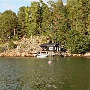 Sommarstuga med bastu och båt vid strandlinjen på Luonnonmaa i Nådendal.