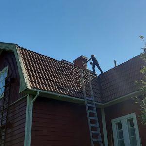 En sotare i svarta kläder står vid en skorsten uppe på ett hustak.