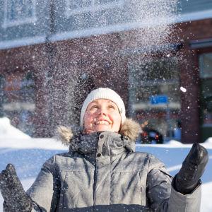 En vinterklädd kvinna ser glad ut och kastar upp snö i luften, snöhögar, trafikmärken och hus i bakgrunden.
