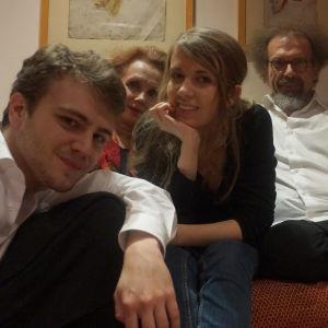 Nelihenkinen perhe istuu sohvalla ja katsovat kameraan.