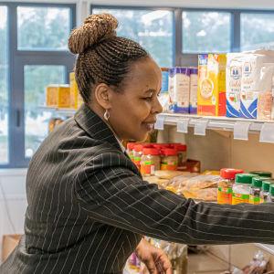 Kvinna radar varor i butikshylla
