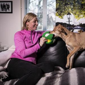 Sohvalla istuva nainen leikittää koiraa pallolla.
