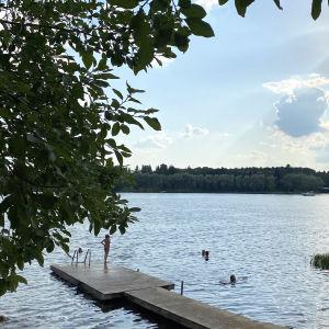 Ihmisiä uimassa järvessä, etualalla uimaranta laitureineen.