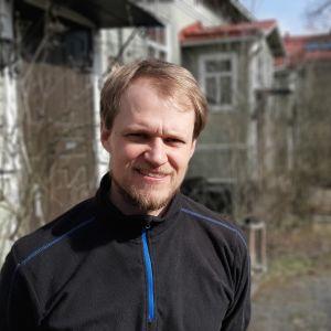 Oskar Lindroos, en man med ljust hår och ljust skägg, står på en innergård med gröna trähus.