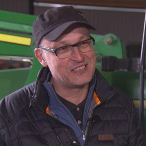 En man i keps och glasögon står framför en traktor