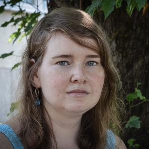Porträttfoto av Mikaela Sallmén taget utomhus sommartid.