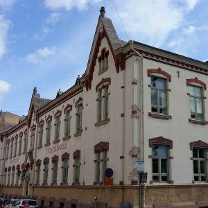 En skola med spetsiga gavlar och vacker tegelstensutsmyckning kring fönstren i ett gathörn i Åbo.