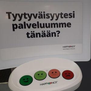Tyytyväisyys palveluihin voidaan ilmaista hymynaamalla esimerkiksi terveyskeskuksen aulassa.