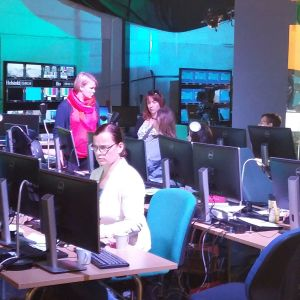 Människor sitter vid datorer i kulisserna till Yles OS-studio.