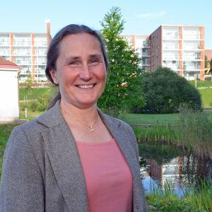 Mona Forsskåhl poserar framför en liten damm och höghus.