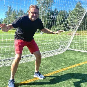 En man med glasögon, shorts och t-shirt står leende och vaktar ett fotbollsmål.