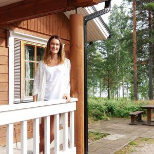 Laura Lönnberg framför en stuga.