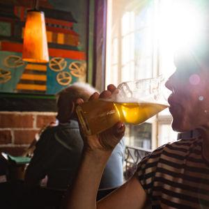 Henkilä juo olutta ravintolassa.