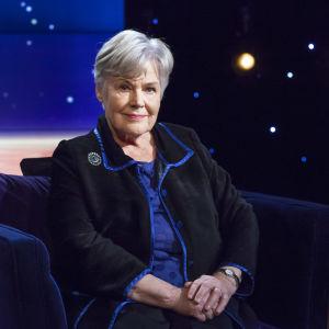 Elisabeth Rehn sitter i en blå sammetsfåtölj hos Daniel Olin.