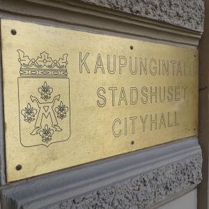 En metallskylt med texten Stadshuset.