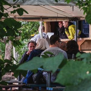 Lummigt uteserveringsområde, människor sitter vid picknickbord, i bakgrunden en ölförsäljning i en gammal kiosk, människor som pratar.
