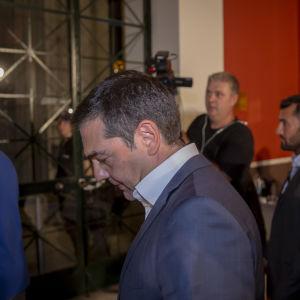 Alexis Tsipras avlägsnade sig med huvudet sänkt efter en presskonferens i Zappeion i centrum av Aten.