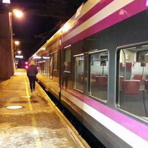 En person går på en perrong där ett lokaltåg står. Det är mörkt ute.