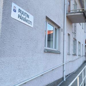 Vaalean kivirakennuksen seinää, jossa kyltti Ruutin päiväkoti. Portaat ja invaramppi johtavat ovelle.