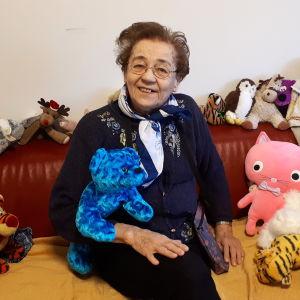 vanha nainen istuu sohvalla pehmolelujen kanssa