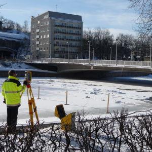 En arbetare med mätinstrument i förgrunden. I bakgrunden den kollapsade Kvarnbron i Åbo.