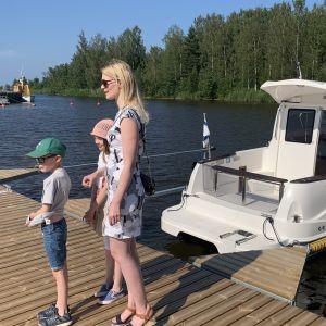 En kvinna går på en brygga med småbåtar, i sällskap av en flicka och en pojke.