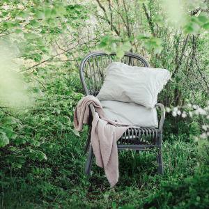 """En tom stol prydd med vita dynor står i en grön trädgård. I nedre högra hörnet syns en logga med texten """"Yle Vegas sommarpratare""""."""