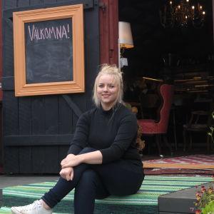 Ellen Järvinen sitter på trappan framför en öppen dörr till till sitt café Källarvinden i Kasnäs