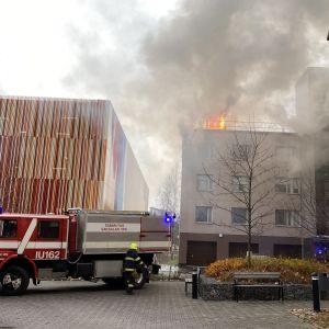 Brandbil framför brinnande höghus. Lågor slår upp genom taket.