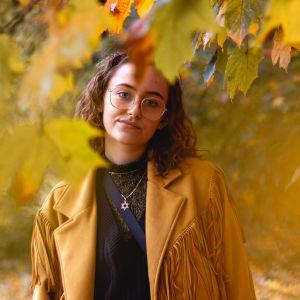 En kvinna står bland gula lönnlöv.