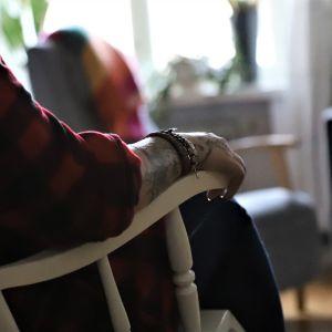 Anonyymi nuori istuu nojatuolissa.