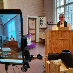 Kamera kuvaa kun pappi puhuu kirkossa