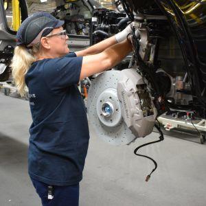 Galina Koskelainen, en dam med blont hår i hästsvans under en blå skyddsmössa, monterar delar på en bil i en bilfabrik.