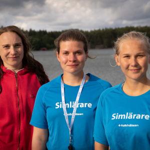 Tre personer på en brygga med havet och en ö i bakgrunden.