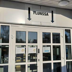 Ingången till en hälsocentral. Över dörren finns en skylt med texten Flunssa.