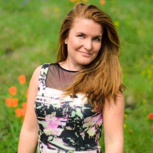 Amie Borgar utomhus framför en blomsteräng.