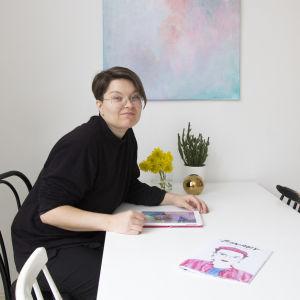 Zarah Holmberg sitter vid ett bord och ritar med sin ipad. På bordet ligger också tidningen hen gjort.