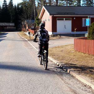 Polkupyöräilijä ajaa kadun oikeaa reunaa
