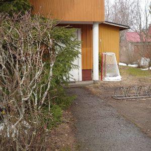 Keväisellä etupihalla näkyy lätkämaali, pyöräteline, roskis ja pusikkoaita