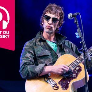 Richard Ashcroft står bakom en mikrofon och spelar gitarr.