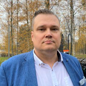 Kempowerin toimitusjohtaja Tomi Ristimäki katsoo kameraan. Seisoo yrityksen takapihalla Lahdessa. Sininen pikkutakki päällään.