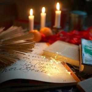Kirjoja pöydällä jouluvaloissa.
