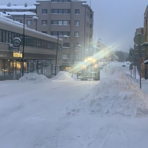 En fronlastare plogar snö i centrum av en liten stad.