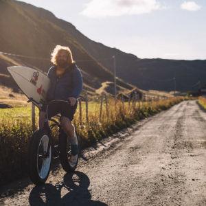 Erik cyklar längs med naturskön sandväg med surfbräda under armen.