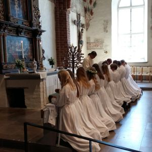Ungdomar i vita kåpor knäböjer och får nattvarden då de konfirmerats i Pargas kyrka.